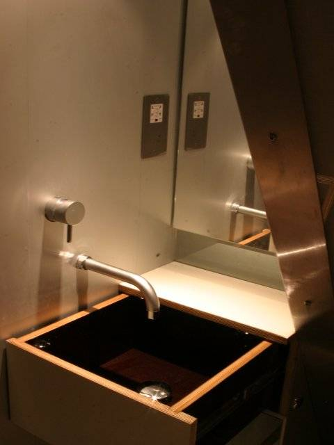 in the small shower room space is maximised by very clean lines, mirrors and the basin in a drawer.